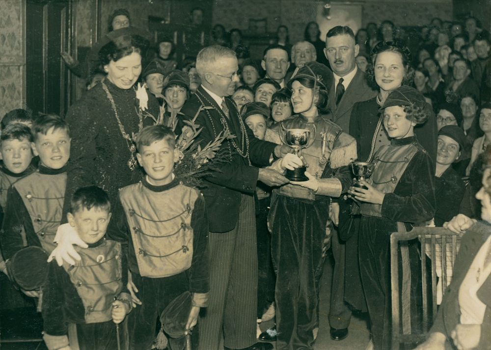 Photo of the Lord Mayor of Newcastle presenting a trophy to children in band uniforms