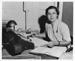 Photo of a woman with a typewriter, open book and pen in hand