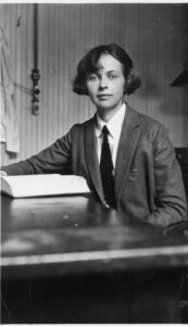 Photo of a woman sitting at a desk with a large book open in front of her